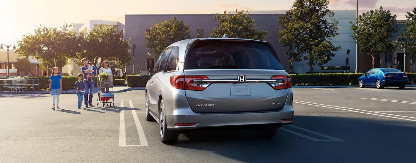 A silver 2019 used Honda Odyssey is shown from the rear outside a store near a family.