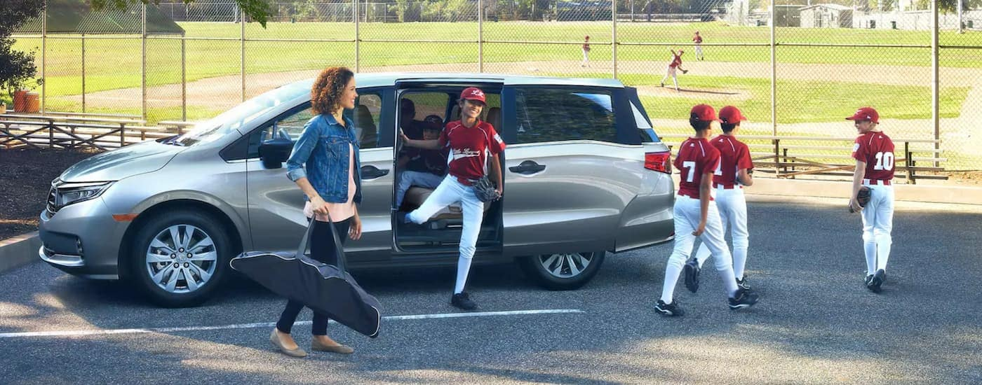 A silver 2020 used Honda Odyssey Elite is shown from the side parked next to a baseball field and youth players.