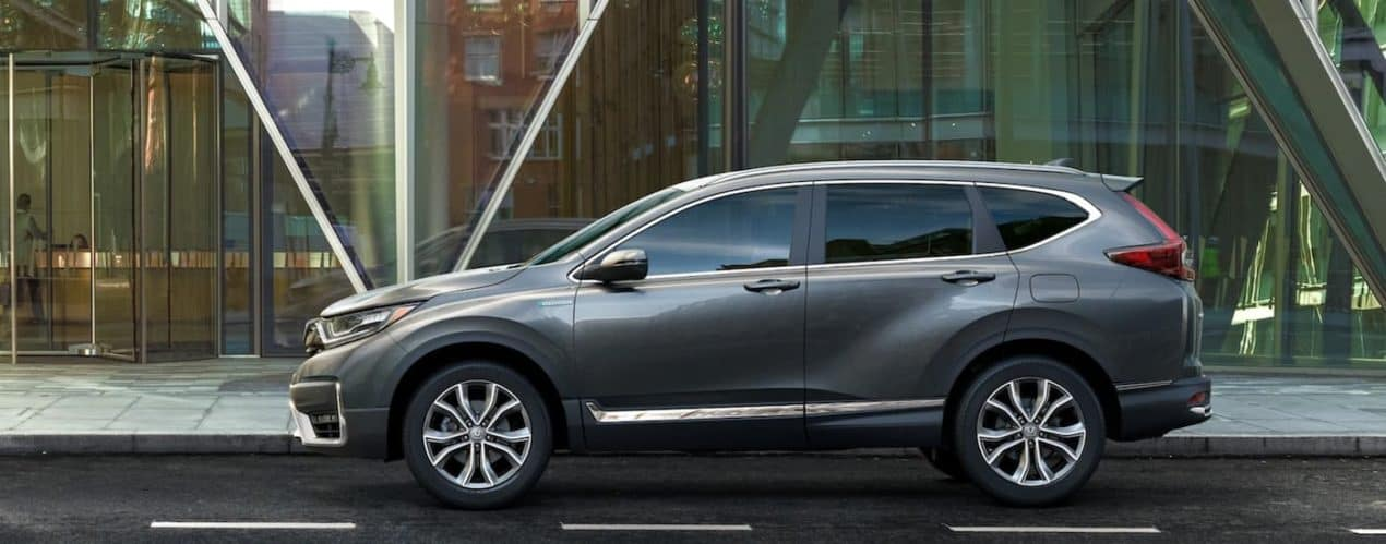 A dark gray 2021 Honda CR-V Hybrid Touring is shown from the side parked in front of a glass and steel building.