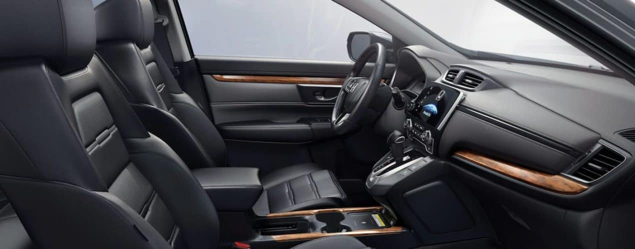 The black and wood grain interior is shown in a 2021 Honda CR-V Touring.