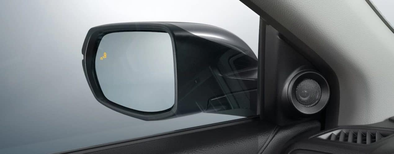 The mirror and blind spot monitoring icon is shown on a grey 2021 Honda CR-V Touring.