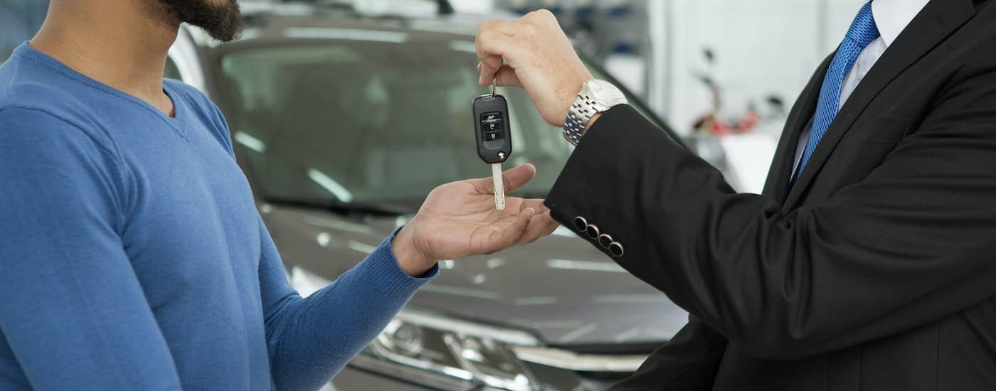 A close up shows a pair of hands exchanging car keys.