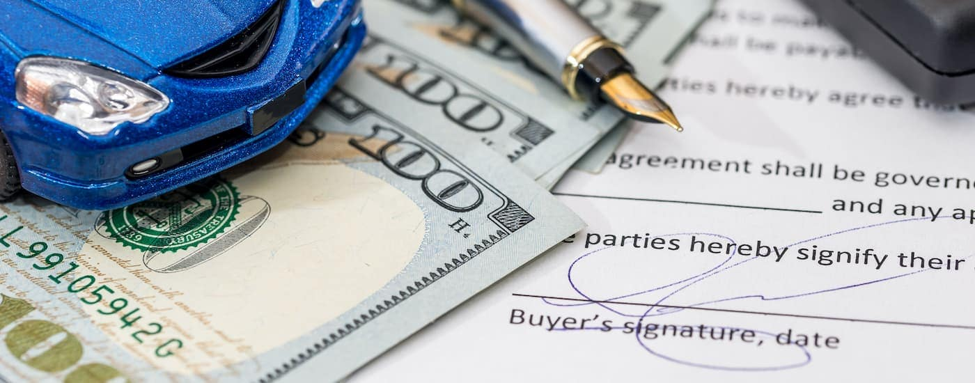 A close up shows signed paperwork, money, a pen, and a blue toy car on a table..