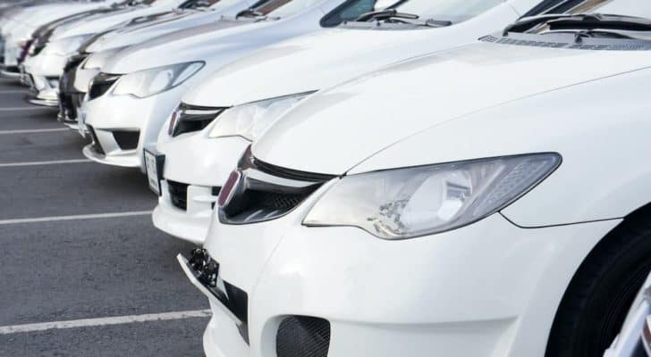 A row of white cars is shown at a certified pre-owned Honda dealer.