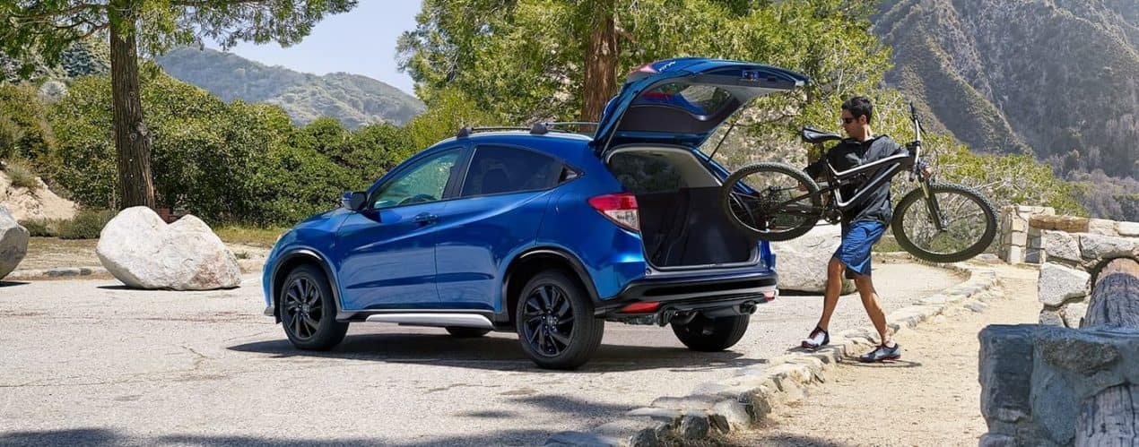 A blue 2021 Honda HR-V Sport is shown from the side with a bike being loaded into the trunk.