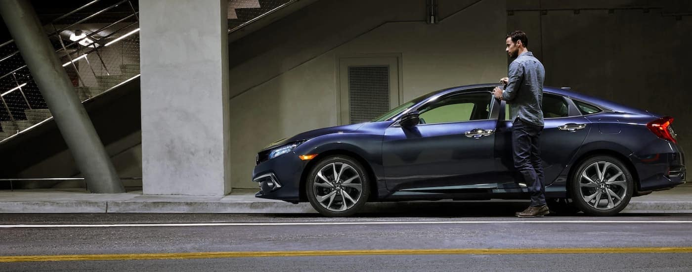 A man is getting in his blue 2021 Honda Civic Sedan Sport on a city street after leaving an Atlanta Honda Civic dealer.
