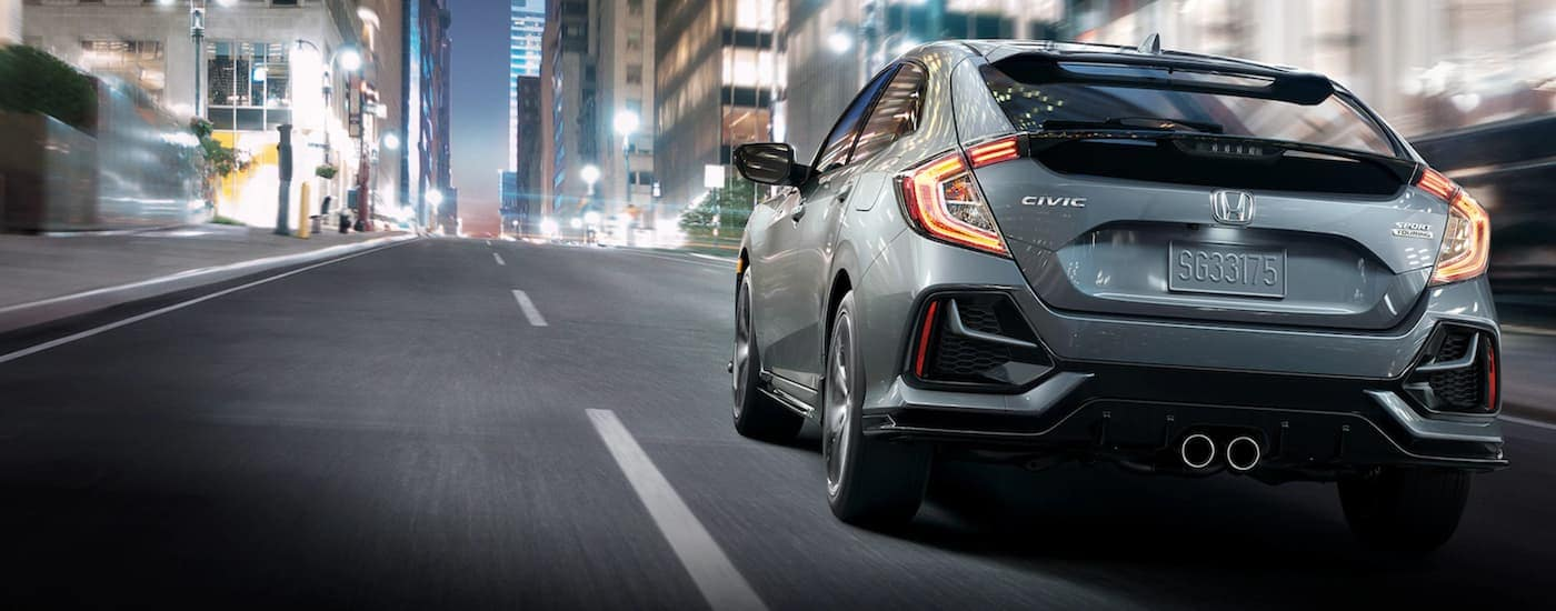 A grey 2021 Honda Civic Hatchback Sport Touring is driving on a city street at night.