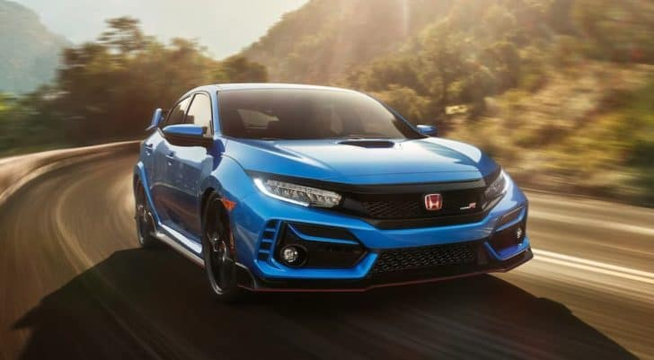 A blue 2021 Honda Civic Type-R is driving around a corner on a sunny road.