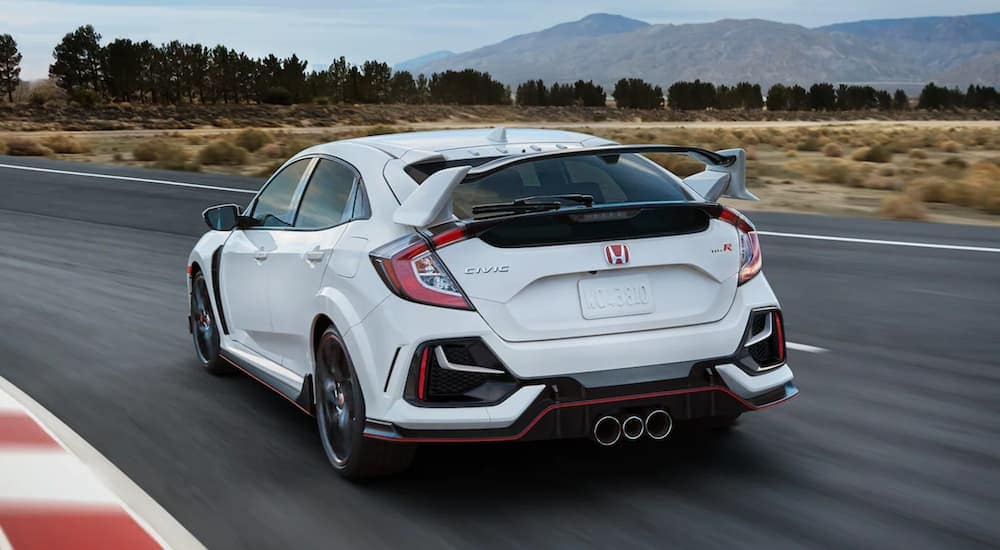 A white 2021 Honda Civic Type R is shown from the back on a racetrack.