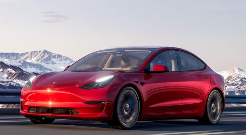 A red 2020 Tesla Model 3 is driving past a snow covered mountain.