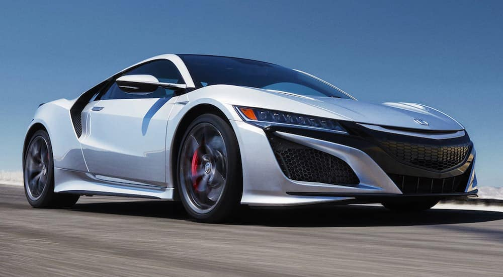 A white used 2020 Acura NSX is shown driving from a low angle after leaving a Atlanta used luxury car dealership.