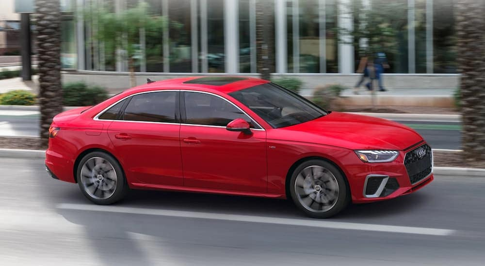 A red 2020 Audi A4 is shown parked on a city street after leaving a Atlanta used luxury car dealership.