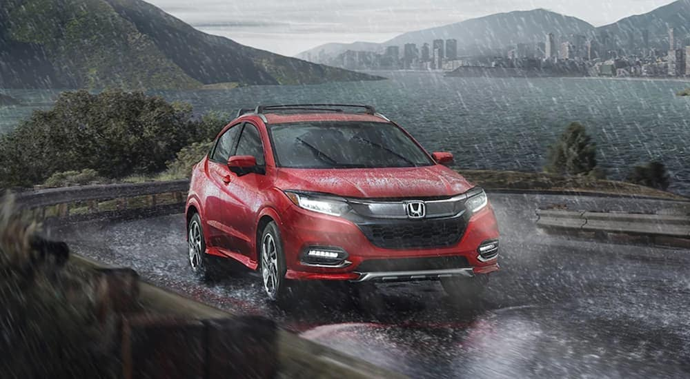 A red used 2020 Honda HR-V is driving through the rain.