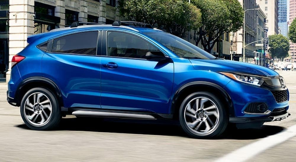 A blue used 2020 Honda HR-V Sport is driving through a city.