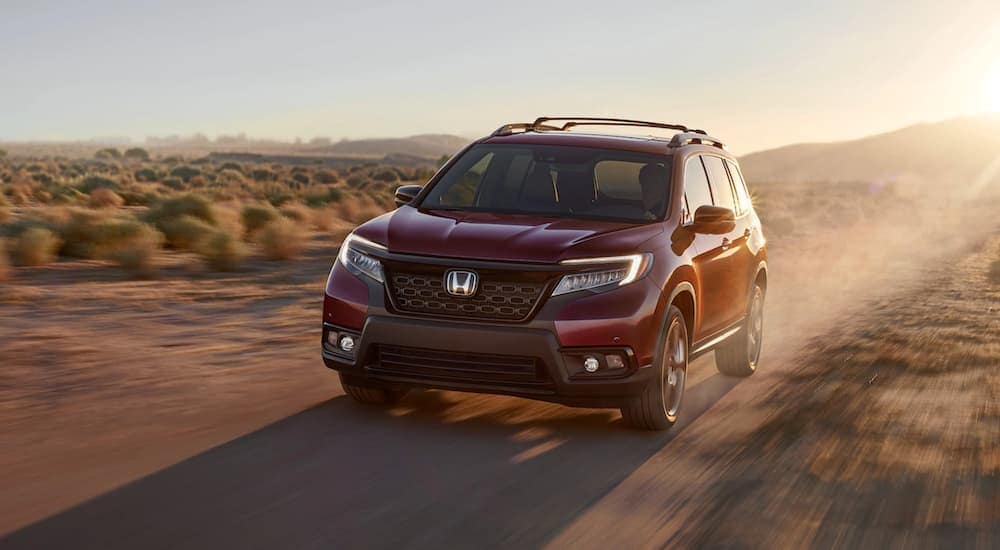 A red used 2020 Honda Passport Elite is shown from the front driving through a field after leaving a Certified Pre-Owned Honda dealer.