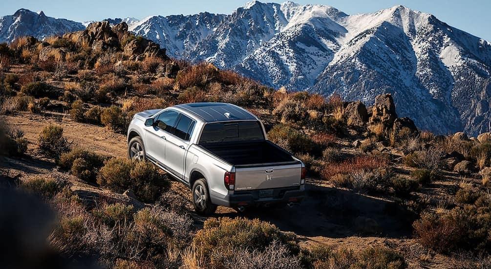 A silver 2021 Honda Ridgeline RTL-E is driving in the mountains after leaving a Honda Ridgeline dealer in Atlanta.