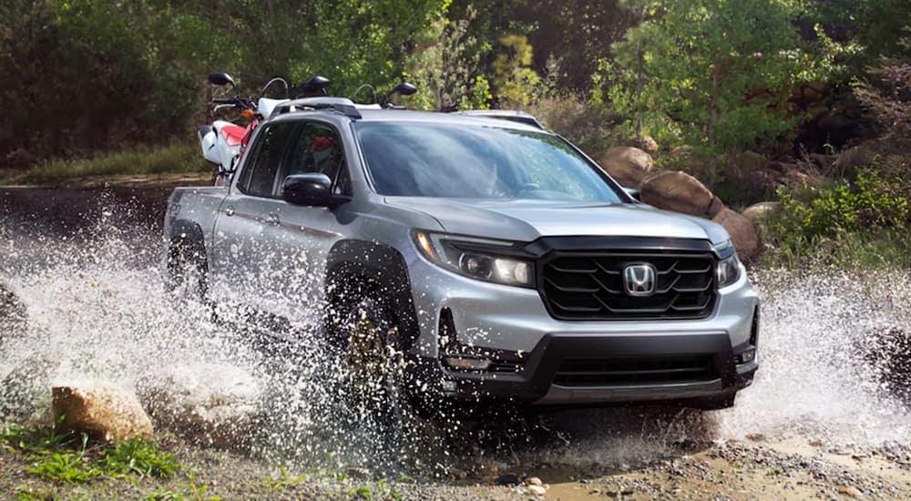 A silver 2021 Honda Ridgeline Sport is driving through a river.