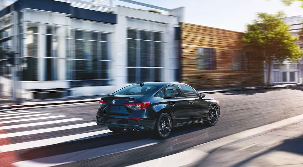 A black 2022 Honda Civic Sport is shown from behind driving through a city after leaving a 2022 Honda Civic Dealer.
