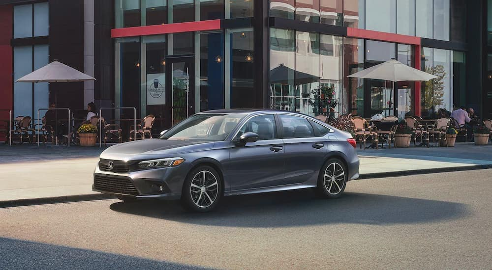 A grey 2022 Honda Civic Touring is shown parked outside a coffee shop.