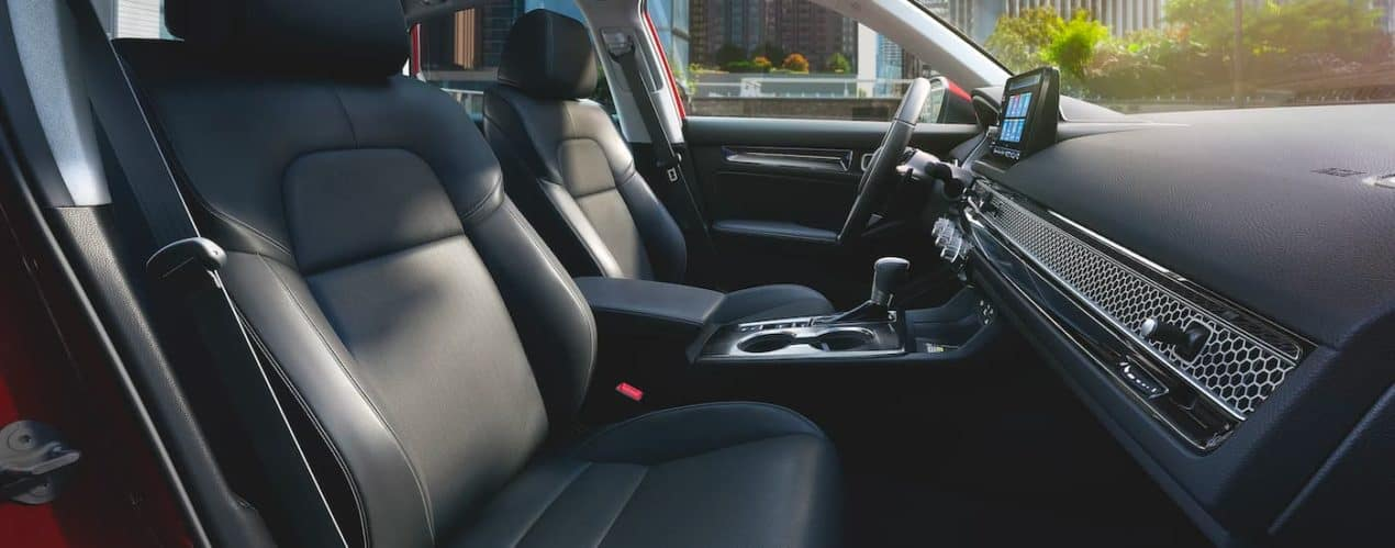 The black front seats and dash are shown in a red 2022 Honda Civic Touring.