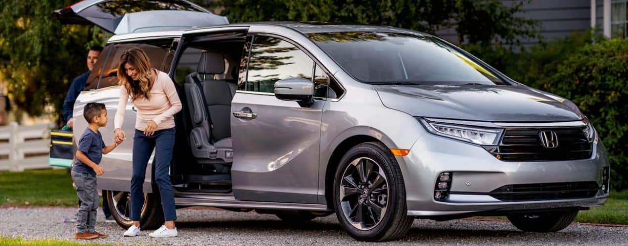 A mother and son are next to the open rear door of a silver 2022 Honda Odyssey after choosing it in the 2022 Honda Odyssey vs 2021 Chrysler Pacifica comparison.