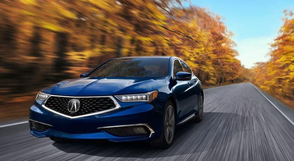 A blue 2020 Acura TLX is shown from the front driving down an open road.