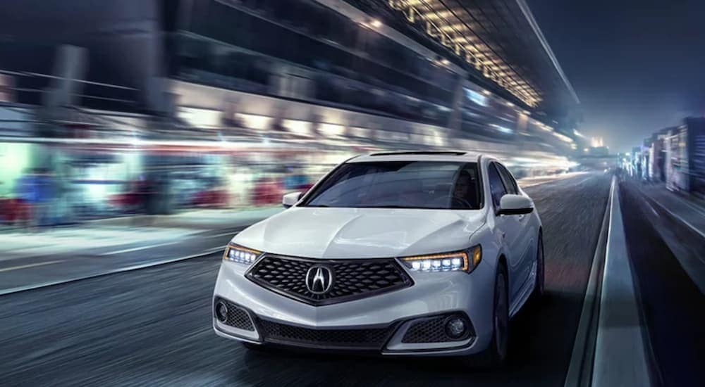 A white 2020 Acura TLX is shown driving through a city at night.