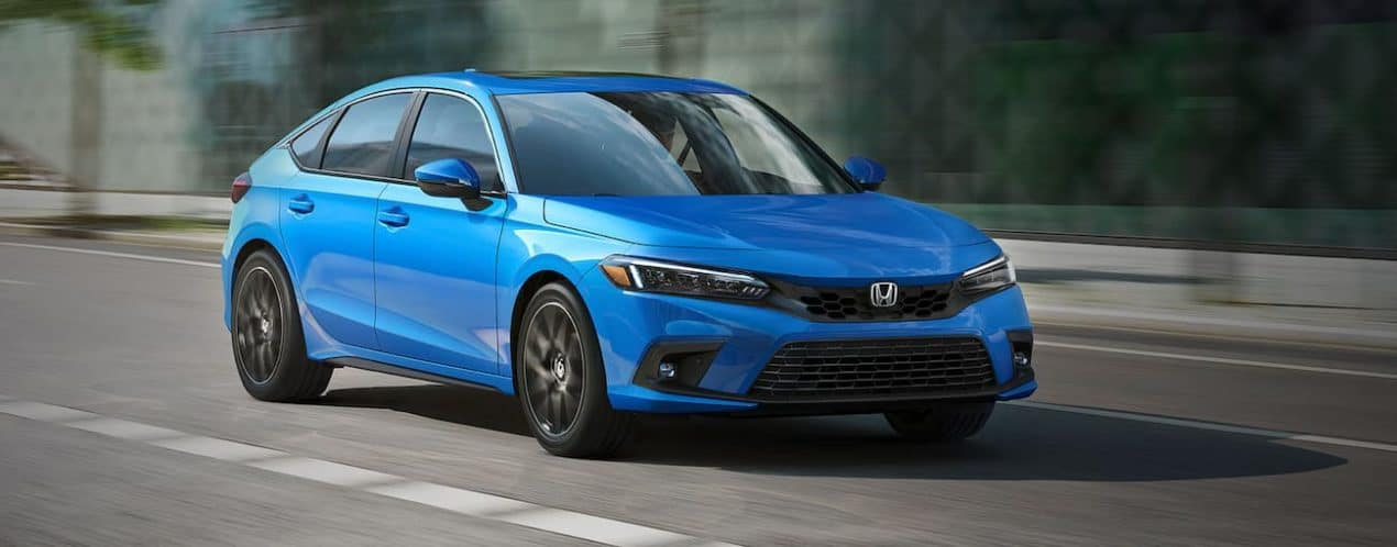 A blue 2022 Honda Civic Hatchback Sport Touring is shown from the front driving through a city.