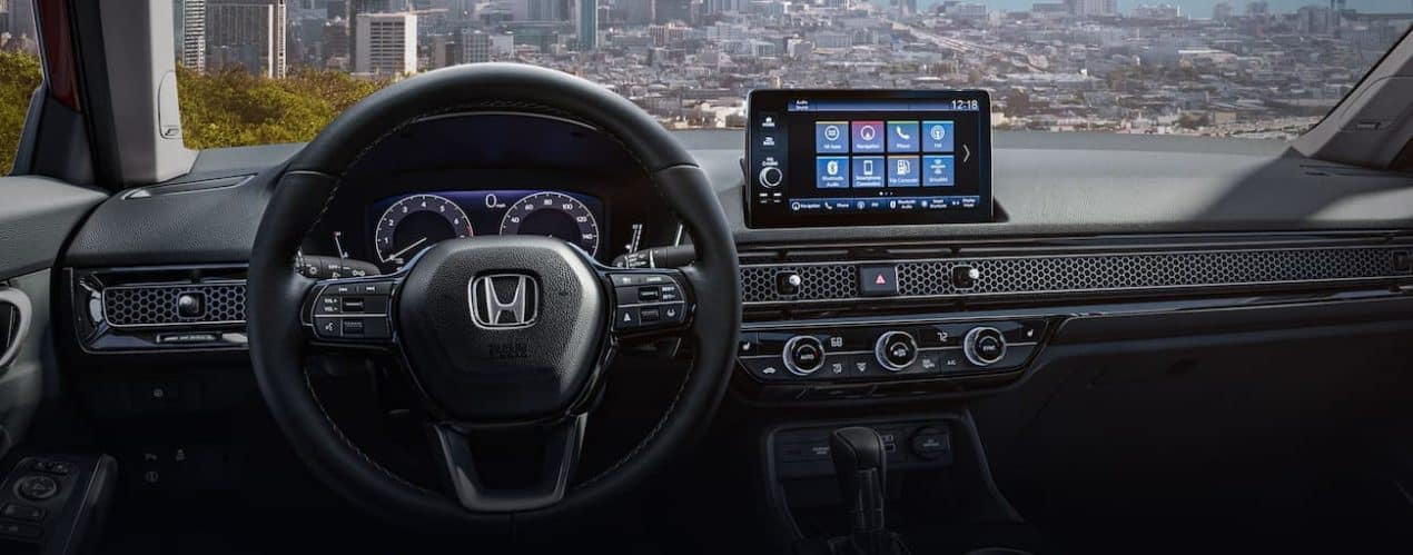 The interior of a 2022 Honda Civic Hatchback Sport Touring shows the steering wheel and infotainment screen.