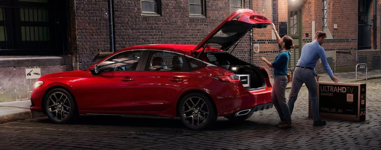 A red 2022 Honda Civic Hatchback Sport Touring is shown with the trunk open.