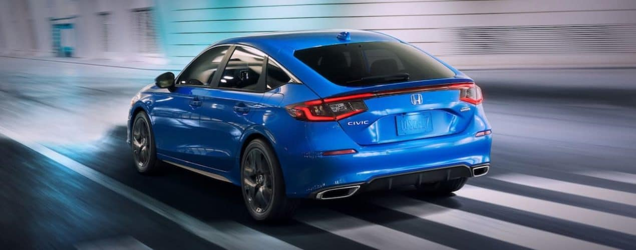 A blue 2022 Honda Civic Hatchback Sport Touring is shown from the rear driving through a city.