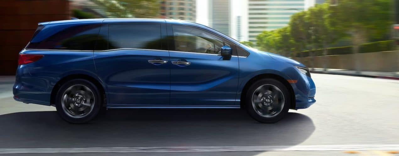 A blue 2022 Honda Odyssey Elite is shown from the side driving through a city.