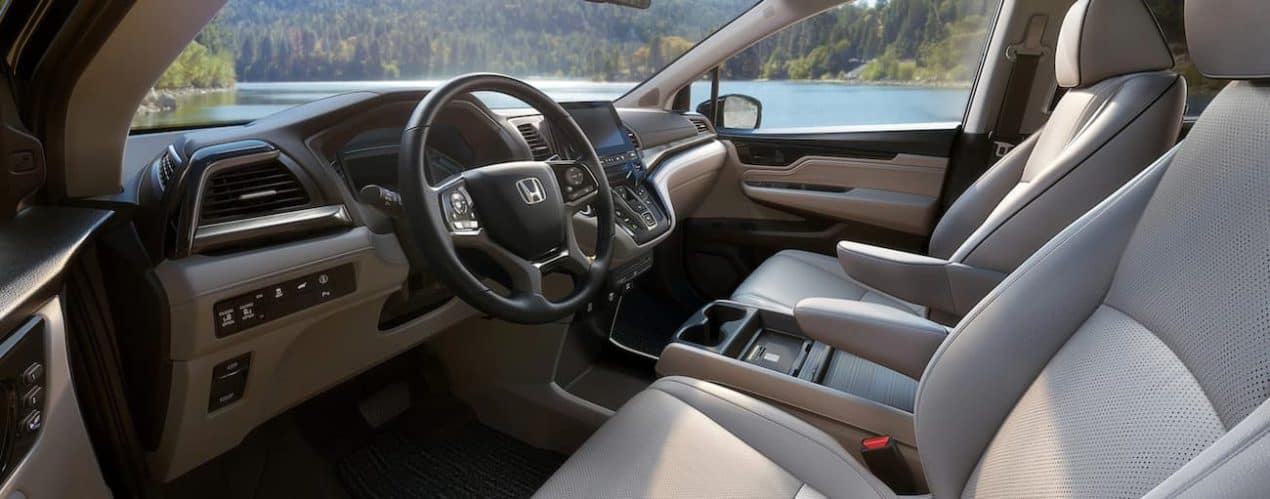 The tan and black interior in a 2022 Honda Odyssey shows the steering wheel and front seats.