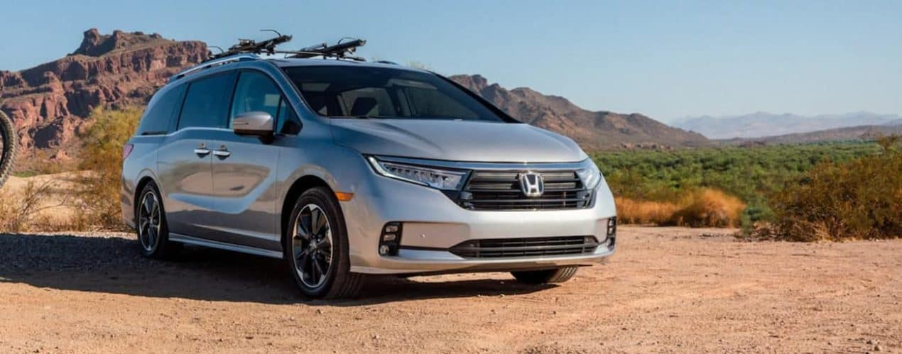 A silver 2022 Honda Odyssey Elite is shown parked in a desert during a 2022 Honda Odyssey vs 2021 Chrysler Voyager comparison.