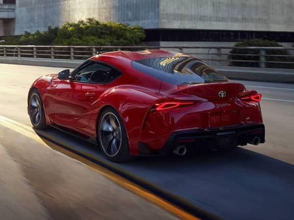 a red toyota coupe driving on the road