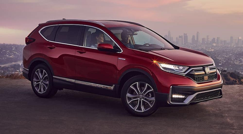 A well known Honda SUV, a red 2020 Honda CR-V Touring, is parked on a hill with a city in the distance.