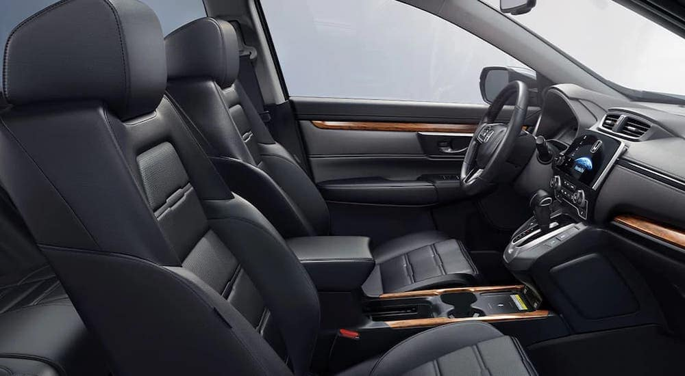 The black interior and seats inside a 2020 Honda CR-V Touring are shown from the passenger side.