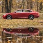 A red 2021 Honda Accord Touring 2.0T is shown from the side parked in front of a pond.