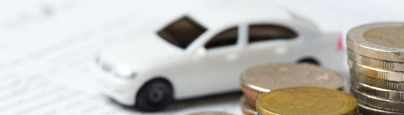 car finance paperwork with tiny car and coins