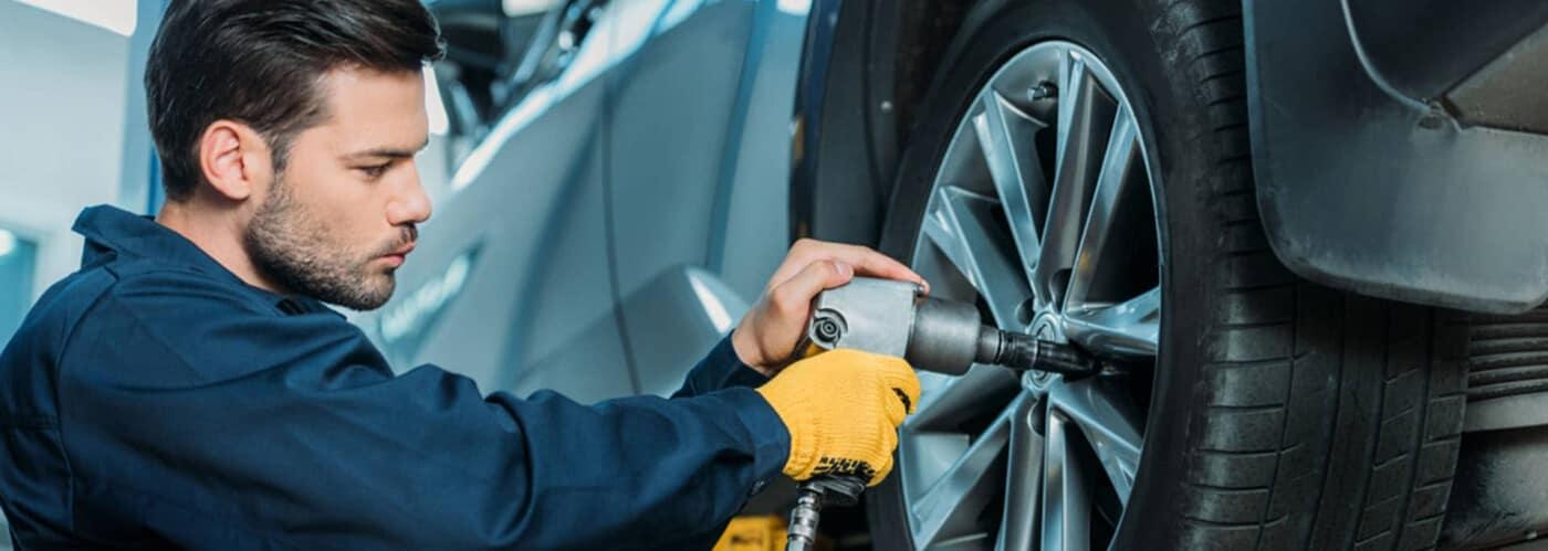 service tech rotating a car tire