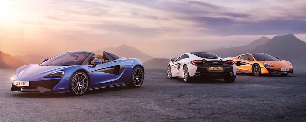 Three McLaren vehicles parked with mountains in background