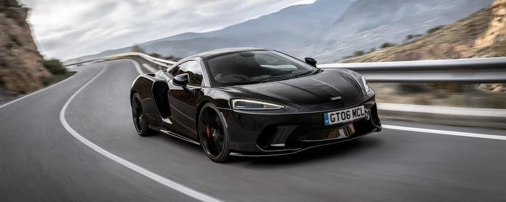 Black McLaren GT driving on mountain highway