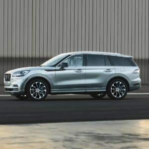 2020 Silver Lincoln Aviator Grand Touring is shown parked next to an airplane hangar