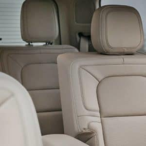 A close up of tan leather trimmed front and second row seats