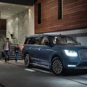 A father son and dog walk up to a 2020 Lincoln Navigator at night