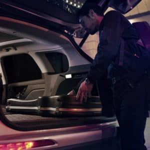 A musician slides his guitar case into the cargo space of a 2020 Lincoln Corsair