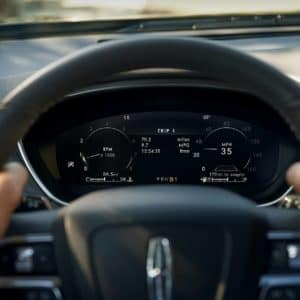 LCD instrument cluster is shown behind the steering wheel