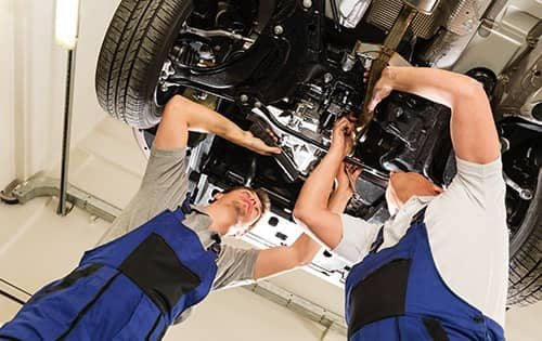 2 Mechanics looking underneath a car